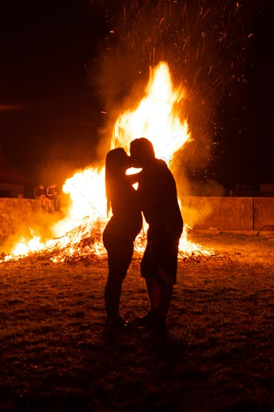 Pregnant couple kissing in front of a fire