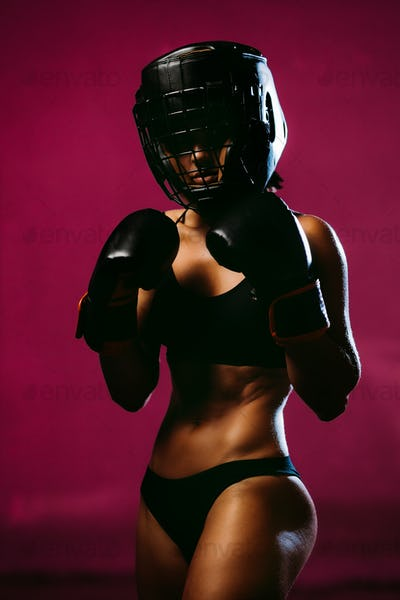 sexy woman fighter in boxing gloves and headgear protective
