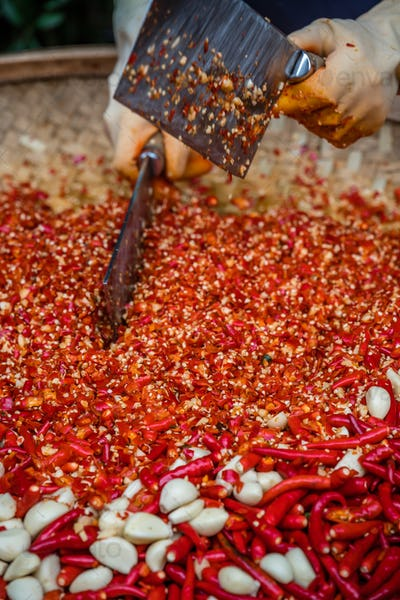 Chillies and garlic being chopped in a wicker bowl