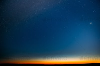 Night Starry Sky With Glowing Stars Above Countryside Field Landscape In Early Spring. Bright Glow