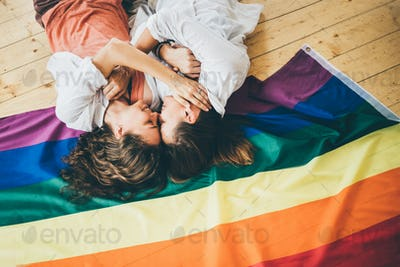 Lesbian couple in love lying and hugging in the rainbow flag.