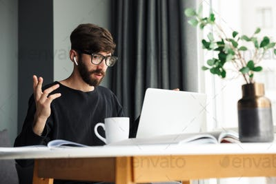 Image of nervous man using wireless earphones and working with laptop