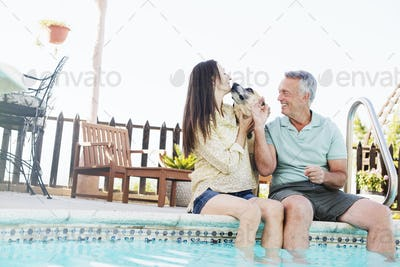 A couple sitting on the edge of a swimming pool, with their dog.