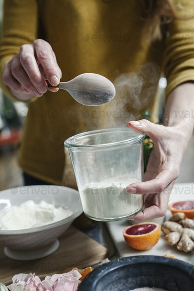 A woman mixing ingredients in a pot, sugar, oranges, petals, and ginger.