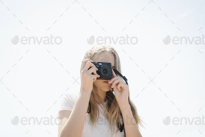 Teenage girl with long blond hair looking through a camera, taking a picture.