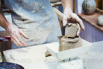 A woman potter working clay measuring it on a weighing scale.
