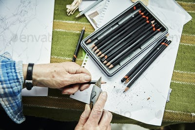 A person using a sharp blade, a craft knife, to sharpen lead pencils. Sketches on paper.