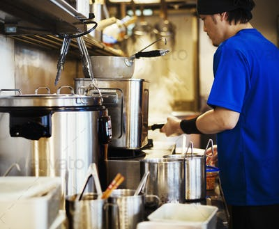 The ramen noodle shop. A chef working in a kitchen.