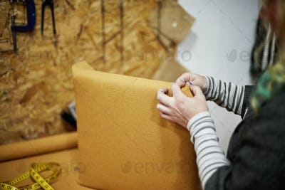 A person fitting a yellow fabric cover to a chair back.