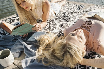 Two blond sisters lying on a jetty, reading a book.