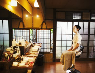 A woman seated on a stool in front of a mirror, a geisha to be made up in the traditional style.
