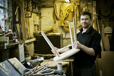 A man working in a furniture maker's workshop. Windsor chairs.