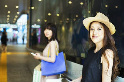 Two young women with long brown hair in a shopping centre.