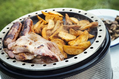 Close up of an English Breakfast being prepared on a camping stove.