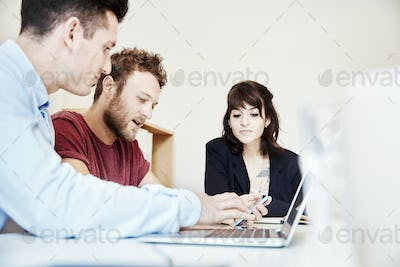 Three people seated at a table at a business meeting using and sharing a laptop screen.