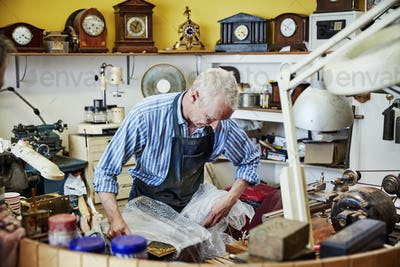 A clock maker busy in his workshop wrapping an antique clock. .