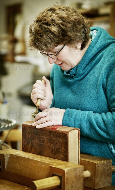 A woman working on the spine of a bound book with a hand tool.
