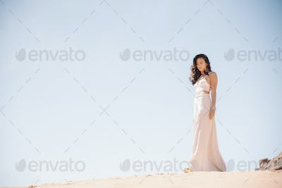 Young woman with long brown hair, wearing a long white dress, standing in a desert.
