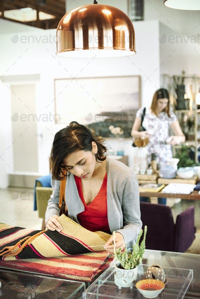 Young woman in a shop, looking at small striped rugs.