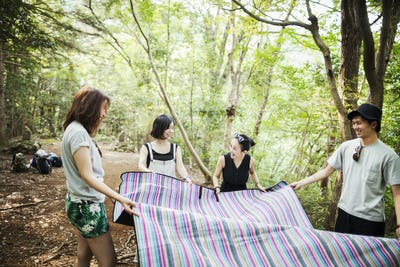 Three young women and man standing in a forest, holding a picnic rug.
