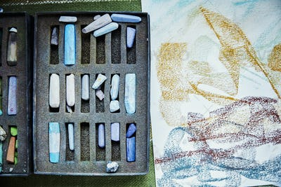 An artist's canvas with an artwork in progress, and box of pastels, colours.