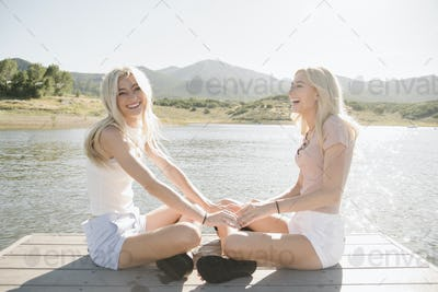 Portrait of two blond sisters sitting on a jetty.