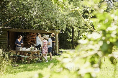 A group of men and women around a lunch table in summer in the shade of trees in a garden.