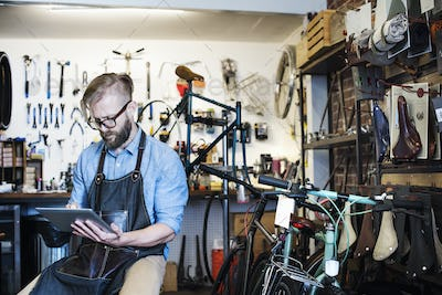 A man working in a bicycle repair shop, seated using a digital tablet.
