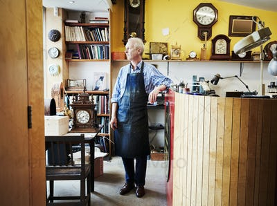A clock repairer, a craftsman standing in his workshop.