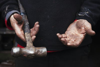 Close up of a blacksmith's hands, holding a metal hammer.