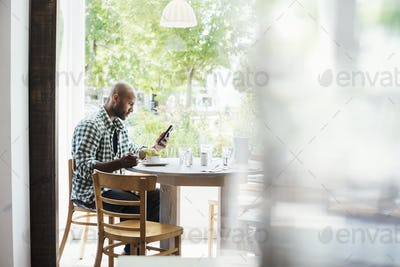 Man wearing a checked shirt sitting in a cafe, using his mobile phone.