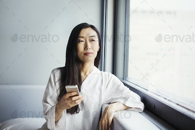 A business woman preparing for work, sitting by a window in her nightclothes, holding a smart phone.