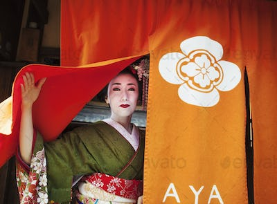 A geisha emerging from a door lifting up the curtain, in traditional kimon and makeup.