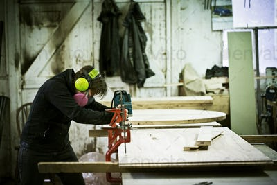 A woman working in a furniture maker's workshop cutting timber with a saw.