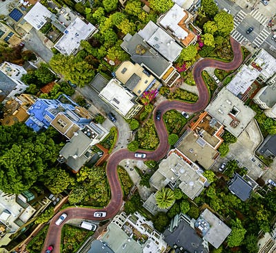 Aerial view of a residential city area, with road descending a hillside with eight hairpin turns.