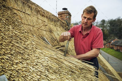Man thatching a roof, inserting a metal peg into the straw.