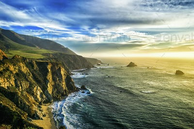 The coastline at Big Sur in california, with steep cliffs and rock stacks in the Pacific Ocean.