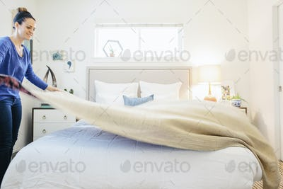 A woman spreading a plain quilt across a double bed  in a light airy apartment bedroom.