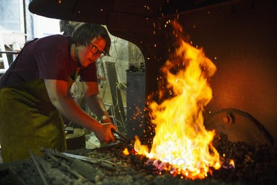 A blacksmith using tongs heats something in a furnace.