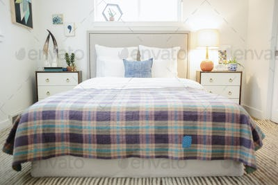 A bedroom in an apartment, double bed covered with a checked purple and cream bed cover