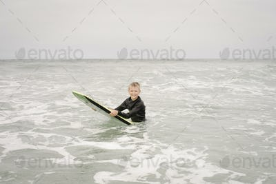 Blond boy bodyboarding in the ocean.