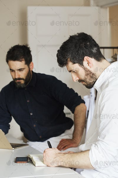 Two bearded men in a bakery, writing in a notebook and working on a laptop computer.