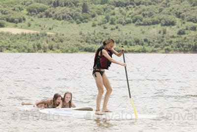 Teenage girl stand up paddle surfing on a lake.