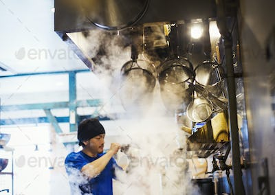 The ramen noodle shop. A chef working in a kitchen with steam rising from the pots of noodles.
