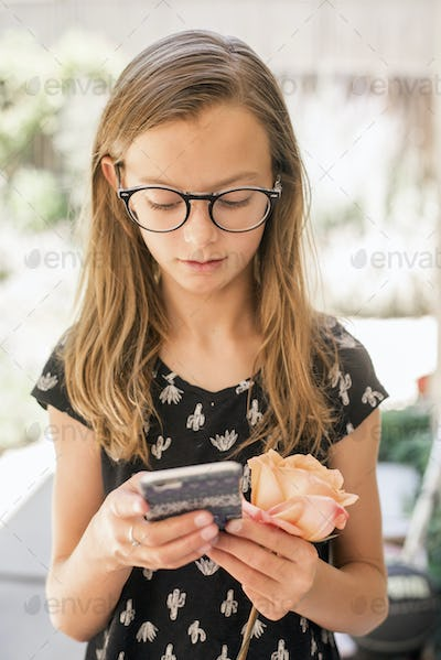 Girl with spectacles holding cellphone and rose.