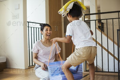 Family home. A woman and her son sorting the laundry, the boy balancing towels on his head.