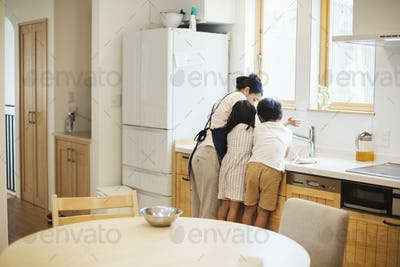 Family home. A mother and two children standing at the sink in a kitchen.
