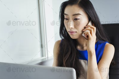 A business woman preparing for work, sitting using her laptop and talking on her smart phone.