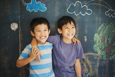 Children in school. Two boys standing with their arms around each other's shoulders by a chalkboard.