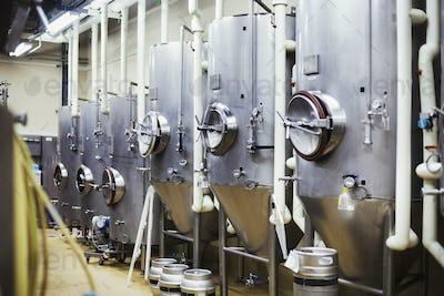 Row of large metal beer tanks in a brewery.